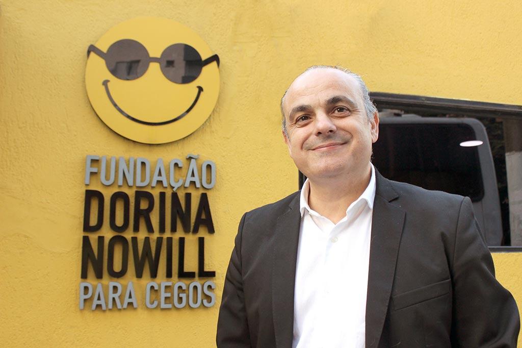 Descrição da imagem: foto de Marcelo Panico à frente da fachada da Fundação Dorina. Ele usa terno preto, camisa branca, olha pra frente e sorri. Ao fundo, uma parede amarela com o logotipo da Fundação Dorina.