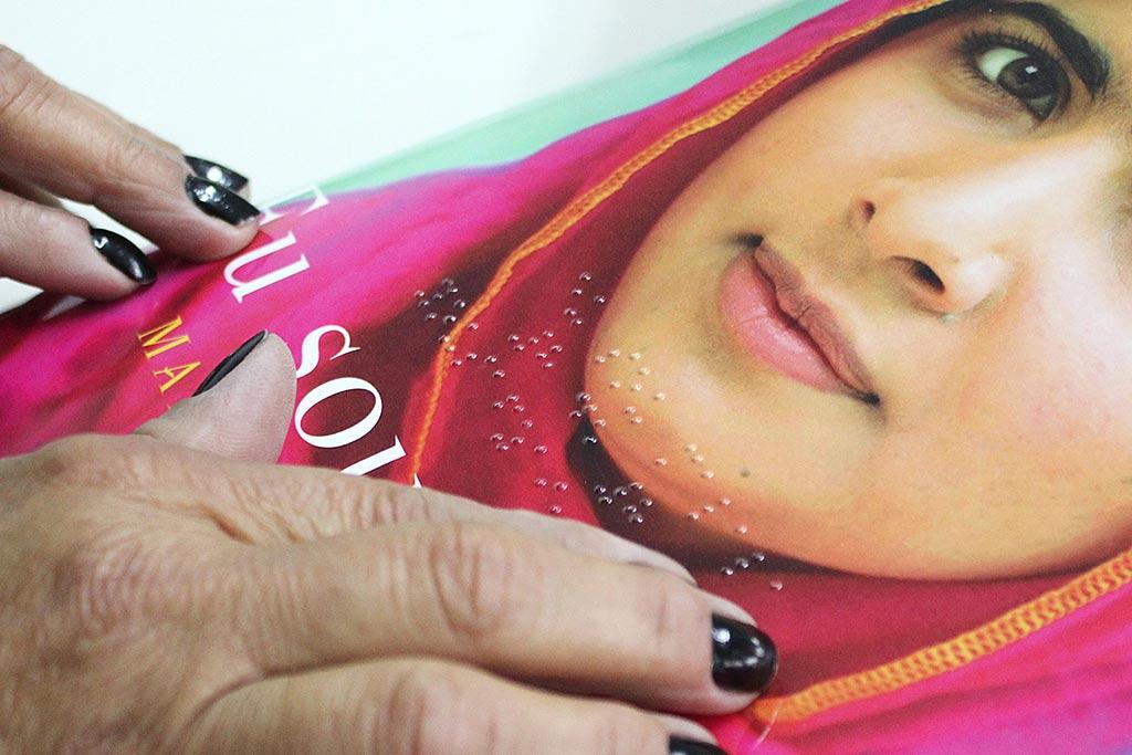 """Descrição da imagem: foto de duas mãos tateando o livro """"Eu sou Malala"""", que tem o rosto da jovem paquistanesa com um lenço rosa."""