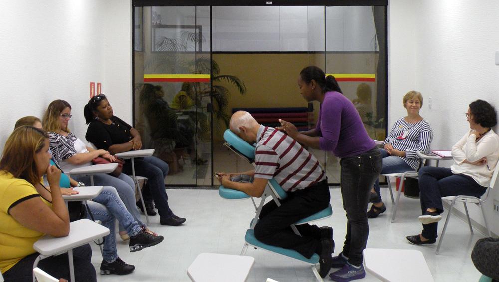 Descrição da imagem: foto de uma mulher fazendo massagem nas costas de um senhor, que está sentado numa cadeira de massoterapia em uma sala de paredes brancas e porta de vidro. Ao redor deles, sete pessoas sentadas em cadeiras universitárias observam.
