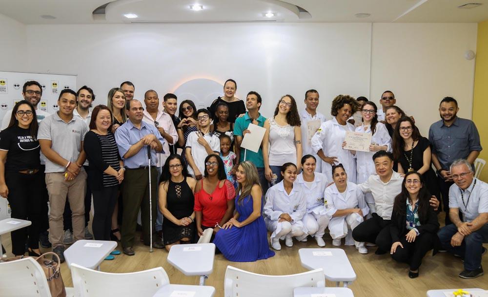 Descrição da imagem: foto de 34 pessoas, entre funcionários da Fundação Dorina e alunos dos cursos profissionalizantes. Eles estão perfilados, alguns agachados, olhando pra frente e sorrindo.