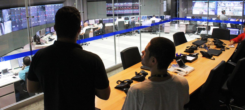 Descrição da imagem: foto de Lucas e um funcionário do metrô no Centro de Controle Operacional do Metrô. Eles estão de costas, olhando, através de uma parede de vidro, para uma sala repleta de painéis eletrônicos e computadores operados por cerca de 10 pessoas.