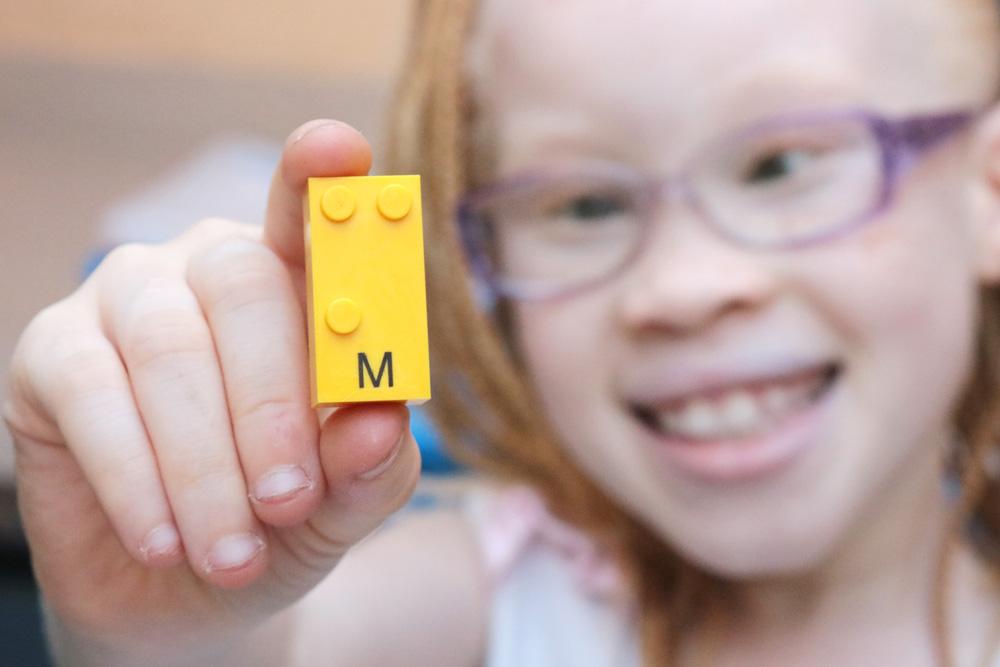 Descrição da imagem: Monica segura peça do Lego Braille Bricks. Ela está segurando a peça de letra M de cor amarela. Ela aparece ao fundo levemente desfocada enquanto mostra a peça para a câmera.