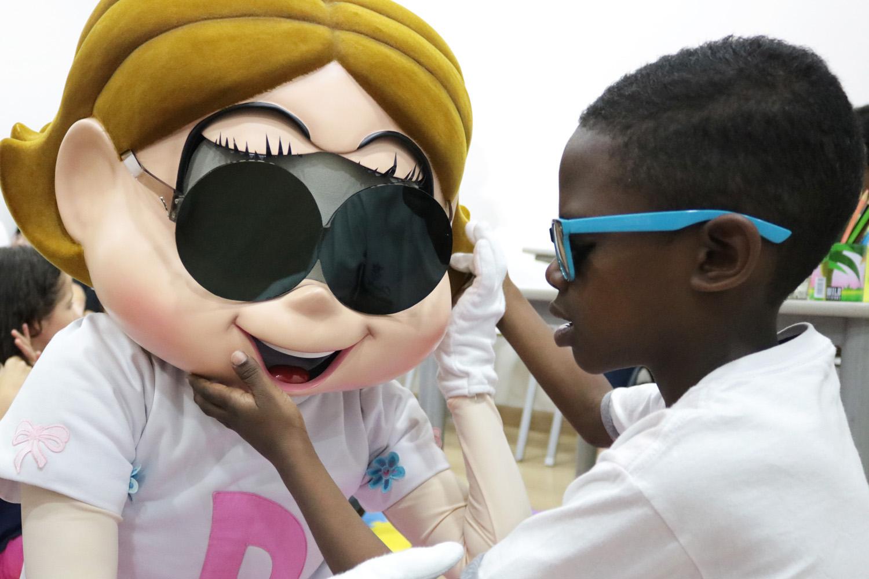 Descrição da imagem: foto de Cristian, uma criança atendida pela Fundação Dorina, tocando o rosto da personagem Dorinha, que segura as mãos do menino.