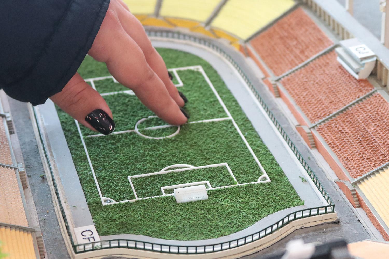 Descrição da imagem: foto da mão de Carla tocando a miniatura do campo do Pacaembu, de aproximadamente 10 cm. Na foto é possível ver também parte das arquibancadas do estádio em miniatura.