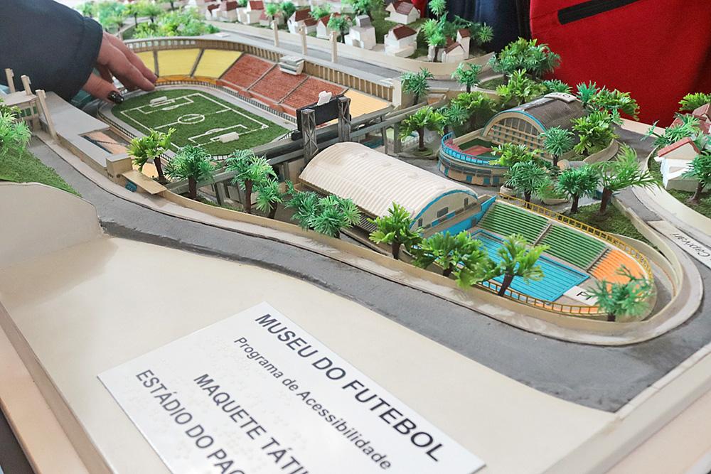 Descrição da imagem: foto da maquete tátil do estádio do Pacaembu, incluindo o clube com piscina e quadras cobertas atrás do campo e as casas da vizinhança.