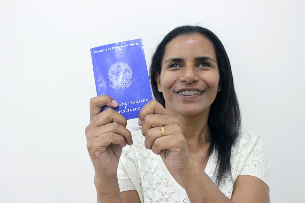 Descrição da imagem: foto de mulher segurando carteira de trabalho, apontando em direção à câmera. Ela olha pra frente e sorri.