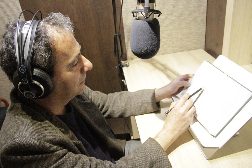 Descrição da imagem: foto de um homem de perfil com um livro aberto à sua frente. Ele toca a página com um lápis, usa fones de ouvido e tem um microfone de estúdio posicionado à sua frente.