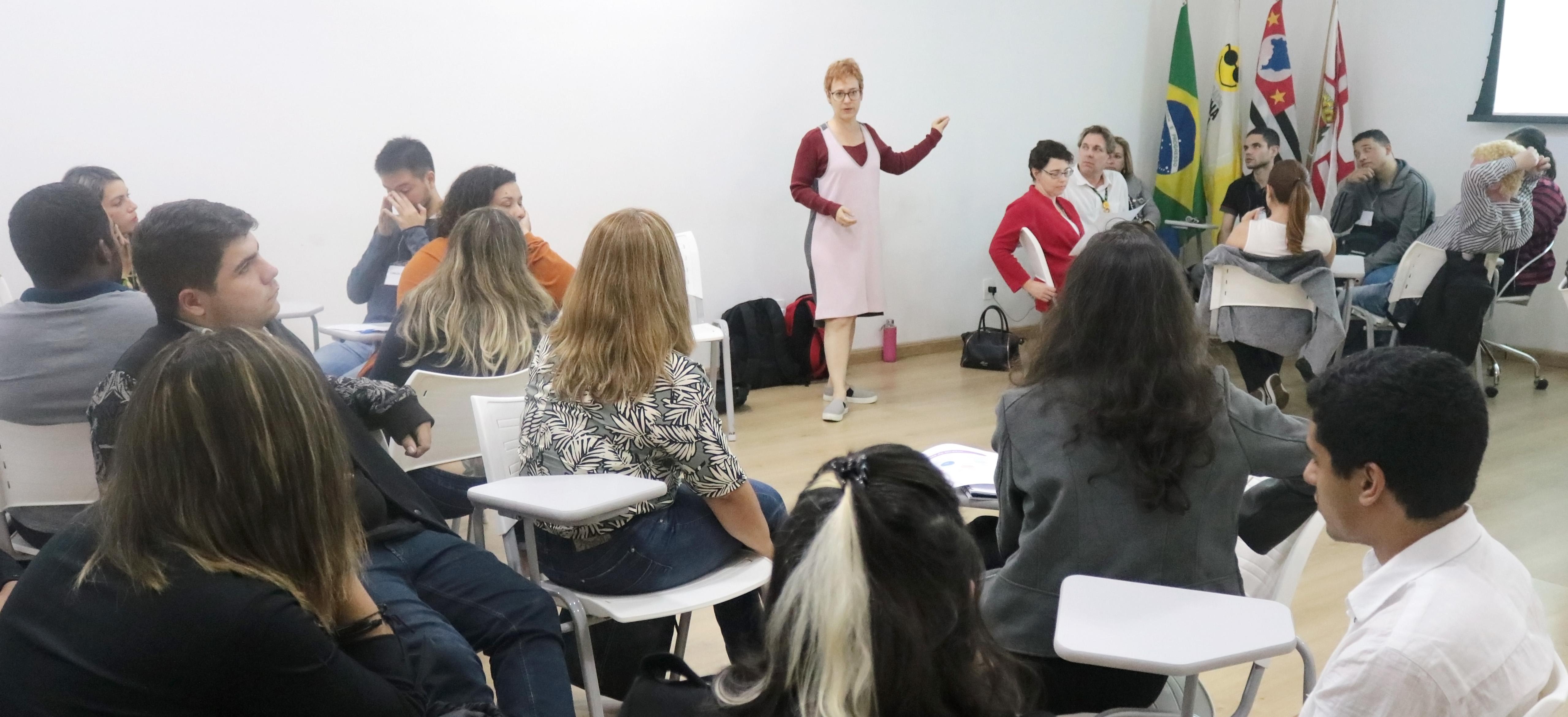 Descrição da imagem: foto de Ivone Santana de pé, falando para cerca de 20 pessoas sentadas, divididas em pequenos grupos.