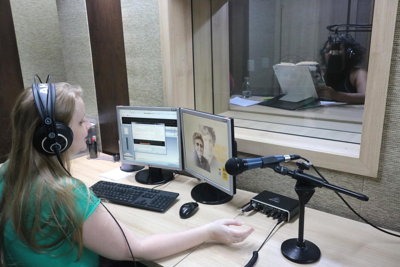 Descrição da imagem: foto de Cláudia Scheer em uma estação de trabalho com computador e microfone. Ela usa fones de ouvido. À sua frente, por uma vidraça, é possível ver a ledora Walkiria Brit dentro do estúdio.