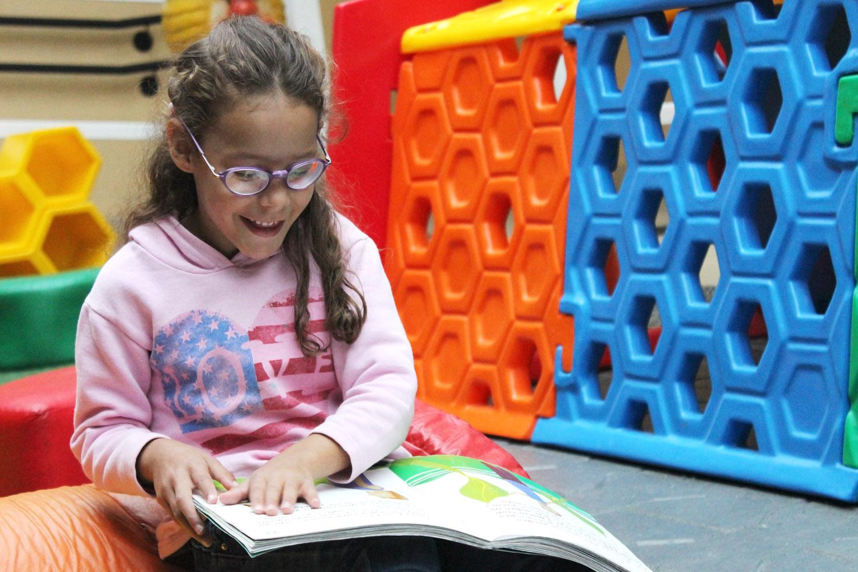 Descrição da imagem: foto de uma garotinha lendo um livro sobre as pernas. Ao fundo há brinquedos coloridos do parquinho da Fundação Dorina.