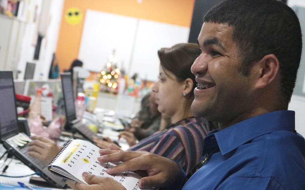 Descrição da imagem: foto de Ademilson de perfil, tateando um calendário e sorrindo, numa estação de trabalho.