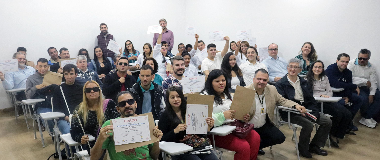 Diversos alunos no auditório da Fundação. Eles estão sentados em cadeiras, olhando para frente com seus certificados dos cursos nas mãos, alguns erguendo-os e outros mostrando-os de frente.