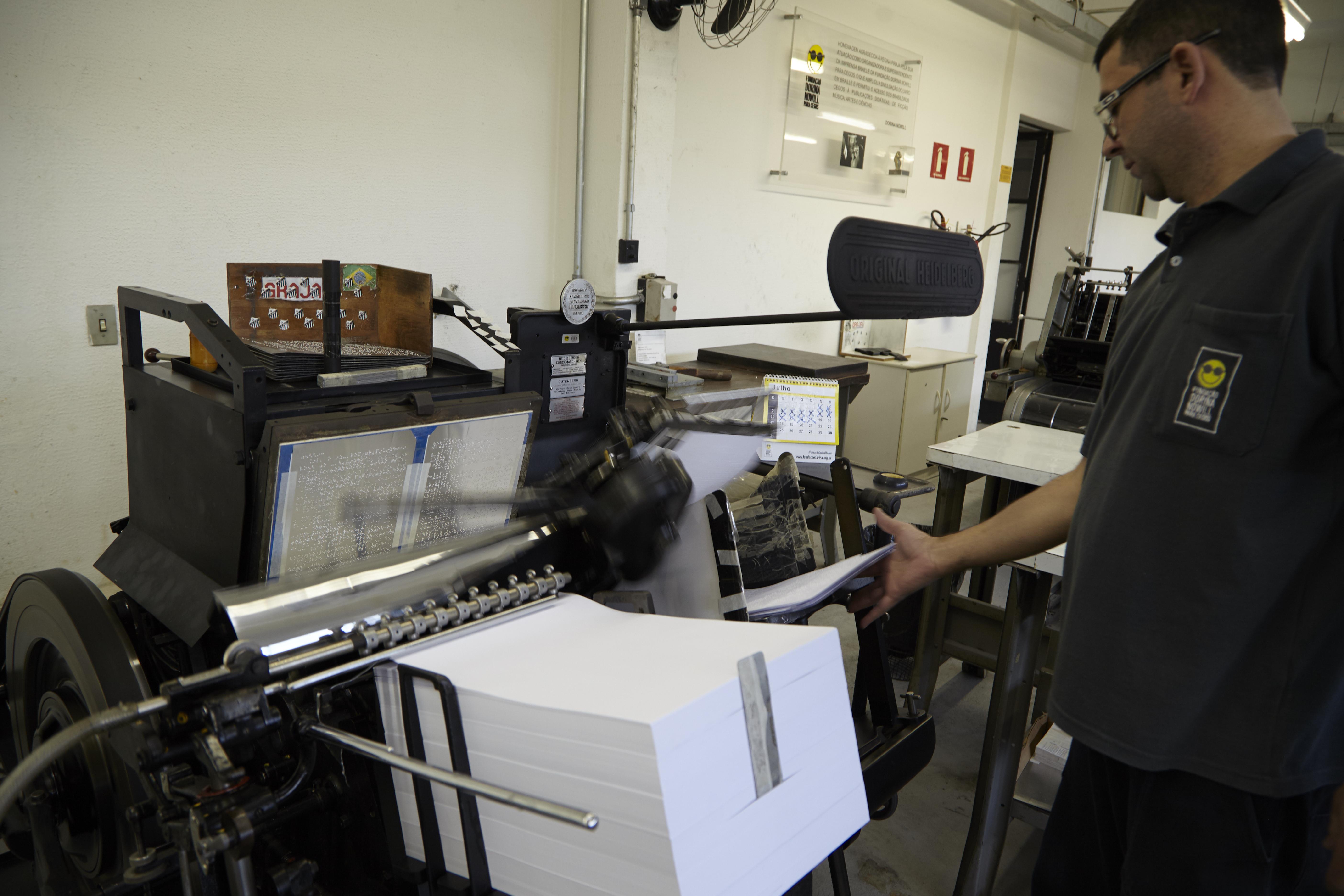 Foto de Ivo, operador da gráfica da Fundação, manuseando uma máquina de impressão em braille. Ele está no canto direito da imagem, vestindo uma camisa preta com o logotipo da Fundação. Ele está de perfil e sua mão direita está esticada até encostar em folhas de papel que estão apoiadas na máquina, que está à sua frente com uma grande pilha de papéis brancos.