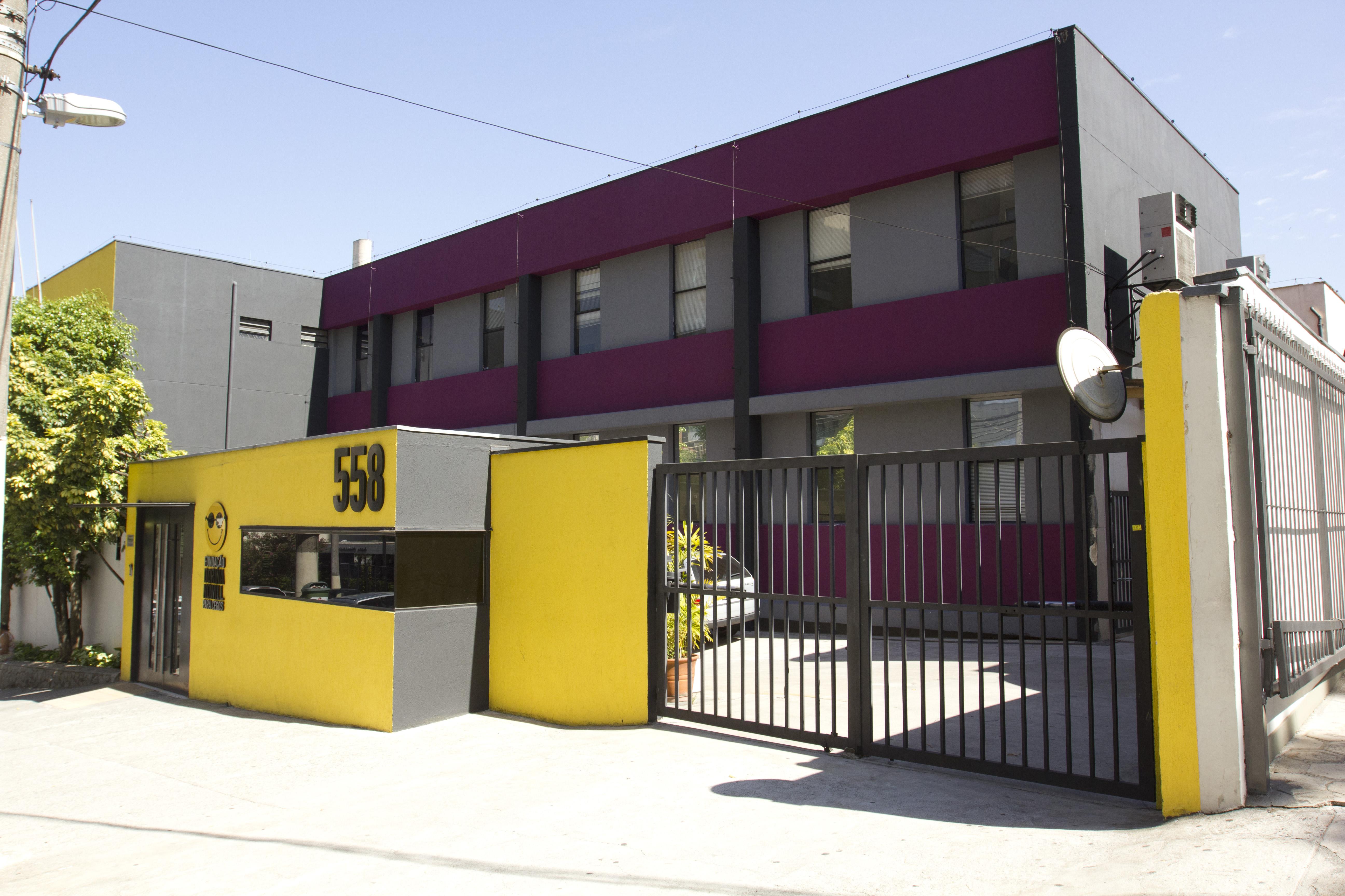 Foto da atual fachada da Fundação Dorina, com destaque para as cores amarela, cinza roxa, com o logotipo da Fundação e o número do prédio em relevos, fixados na parede. de entrada.