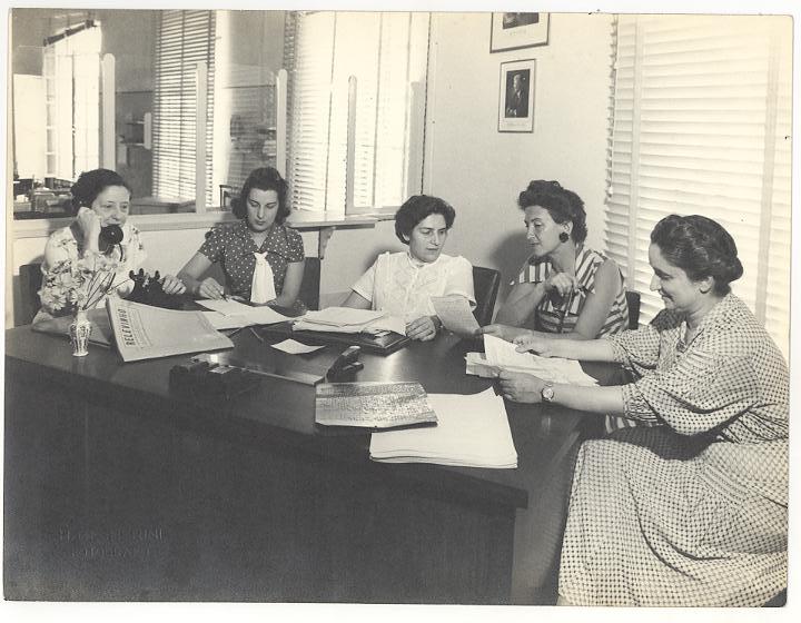 Imagem antiga em preto e branco de cinco mulheres, entre elas Dorina Nowill e Regina Pirajá. Elas estão em um escritório com persianas e parede de vidro ao fundo. As mulheres estão sentadas lado a lado, apoiadas sob uma grande mesa de madeira. Sobre a mesa há diversos papeis e jornais que as mulheres estão consultando e também um aparelho de telefone, que uma das mulheres está utilizando.