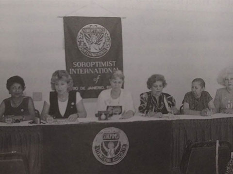 Foto antiga em preto e branco de uma reunião das soroptimistas. Há seis mulheres sentadas lado a lado apoiadas sob uma bancada. Ao fundo, há um banner com o logotipo do Soroptmist Internacional.