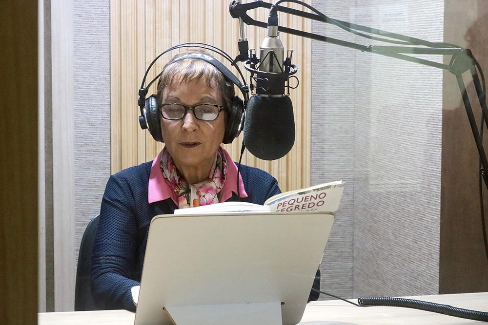 Descrição da imagem: foto de Heloísa Schurmann com um livro aberto sobre prancheta à sua frente. Ela usa fones de ouvido e tem um microfone de estúdio posicionado à altura do rosto.