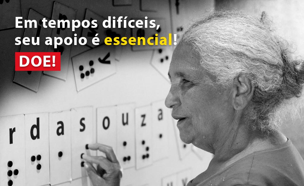 """Descrição da imagem: foto em preto e branco de uma senhora de cabelos brancos de perfil, tocando um painel na parede com o alfabeto em braille. Ao lado esquerdo há o texto """"Em tempos difíceis, seu apoio é essencial. Doe!"""""""