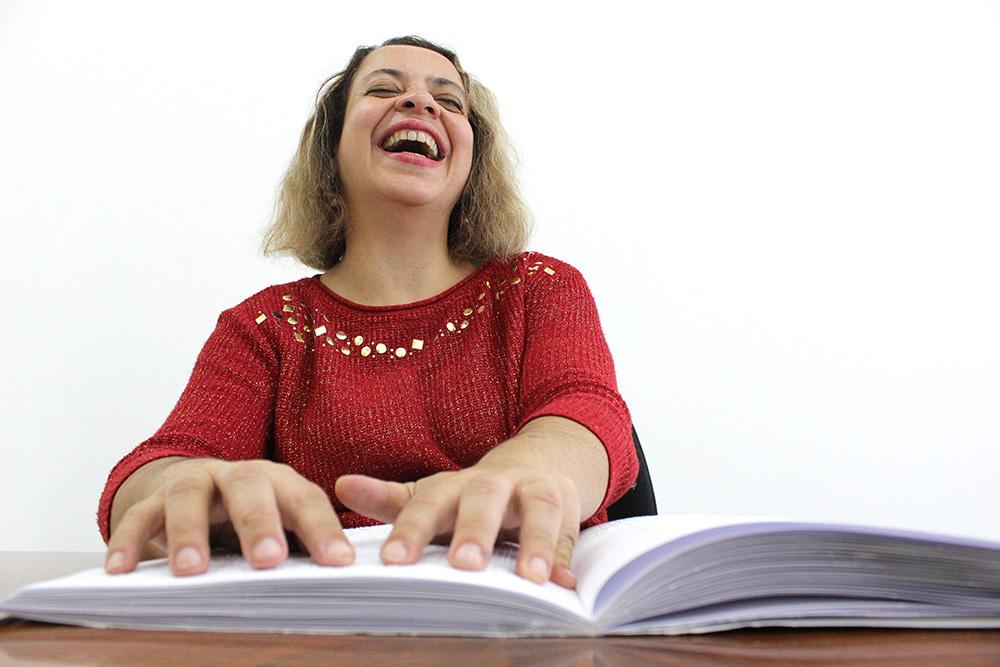 Descrição da imagem: foto de mulher tateando um livro em braille aberto sobre a mesa e sorrindo.