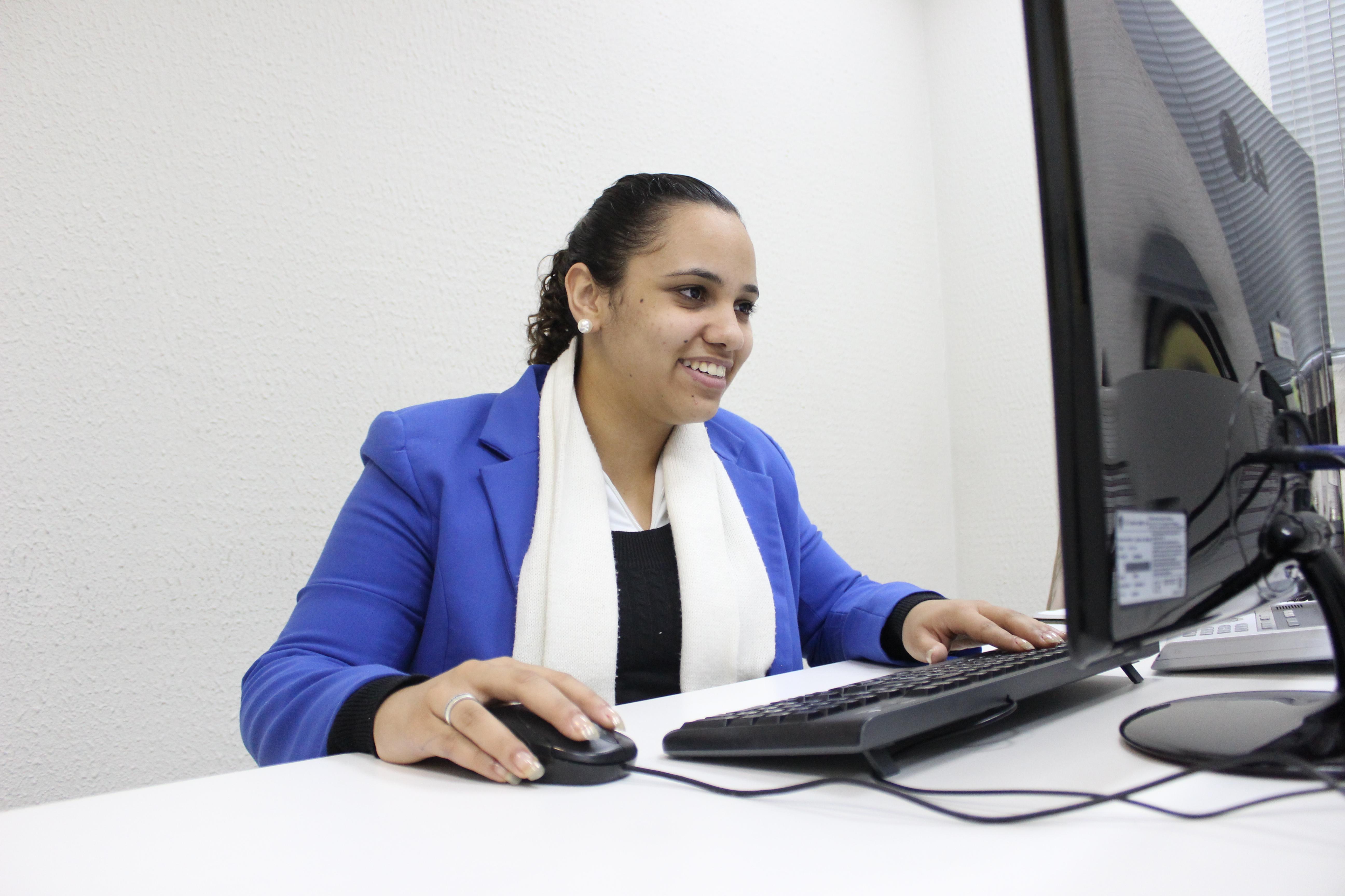 Foto de Stephanie, cliente atendida pela Fundação. Ela está sentada em frente a uma mesa branca, com uma tela de computador a sua frente. Suas mãos estão sb um teclado e um mouse pretos. Stephanie veste bleaser azul e cachecol branco e sorri.