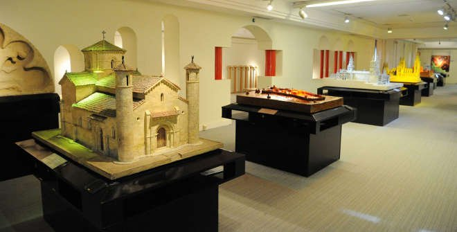 Imagem de uma sala de exposições do Museu da ONCE. Há várias mesas pretas perfiladas e sobre cada uma delas há uma obra em escultura, em sua maioria de castelos e grandes construções.