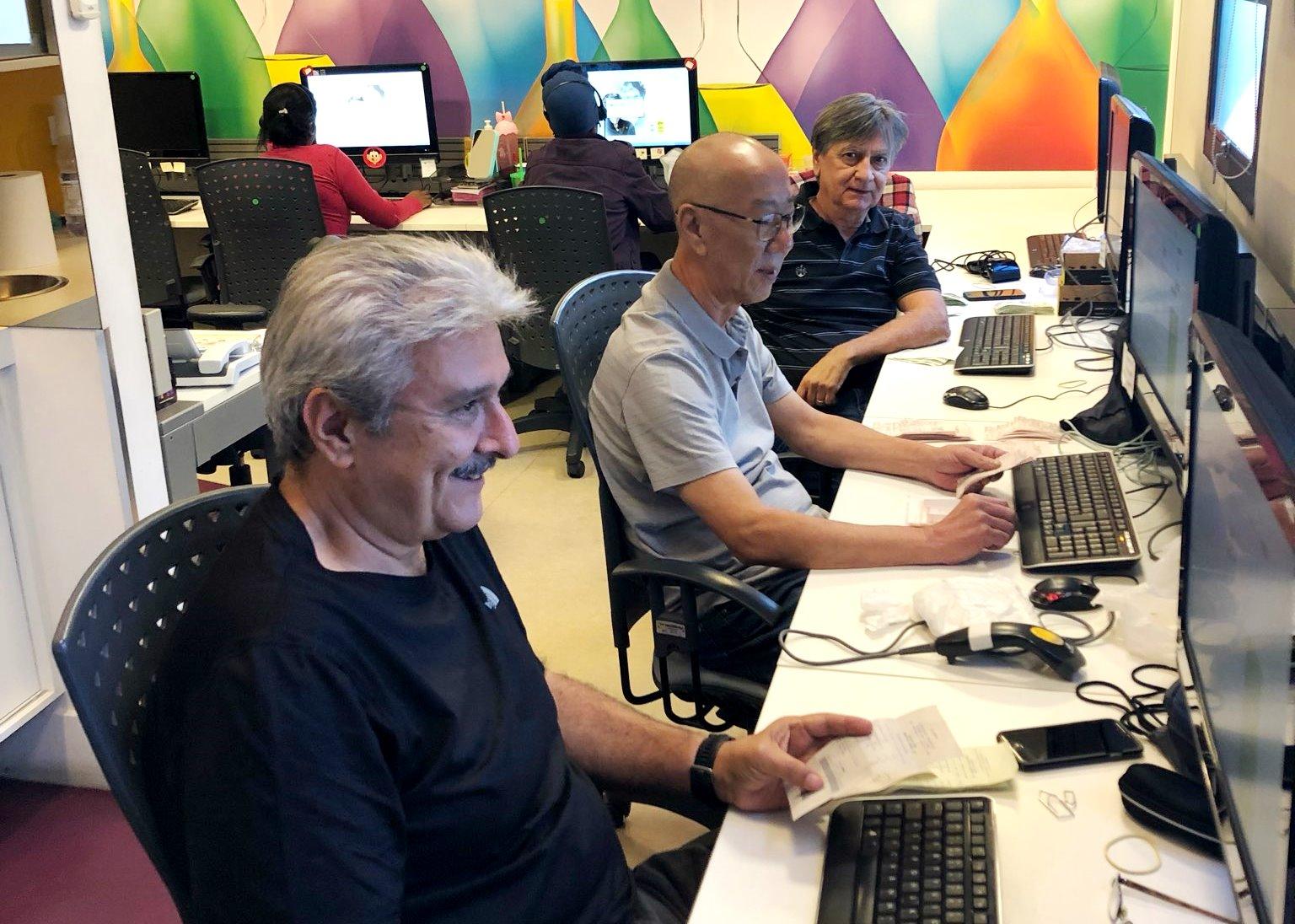 Foto de uma sala com paredes coloridas. Á direita há uma bancada banca com diversos computadores e três homens sentados de perfil, em frente à bancada e outras duas pessoas ao fundo, sentados de costas para quem visualiza a foto. Sobre as mãos dos homens estão cupons fiscais para digitação.