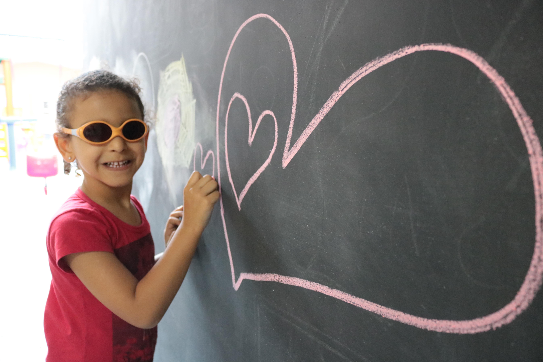 Descrição da imagem: foto de menina sorridente de óculos escuros. Ela segura um pedaço de giz sobre um quadro negro onde está desenhado um coração na cor rosa.