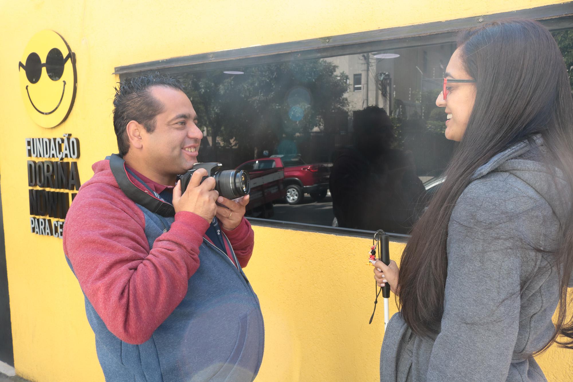 Descrição da imagem: foto de Marco Oton tirando uma foto de sua esposa Cíntia. Eles estão de perfil, de frente um para o outro e sorrindo. Marco tem uma câmera fotográfica posicionada abaixo do queixo. Ao fundo há uma parede amarela com o logotipo da Fundação Dorina.