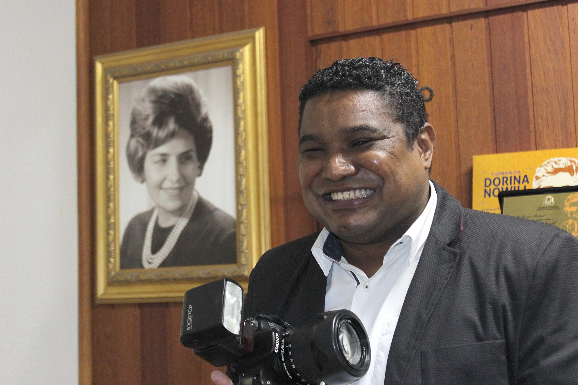 Descrição da imagem: foto de João Maia sorridente empunhando uma câmera fotográfica na altura do peito. Ele é negro, tem cabelos curtos e veste camisa branca com terno preto. Atrás dele há um retrato em branco e preto de Dorina Nowill na parede.